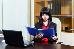 Attractive businesswoman sitting at workplace in the office, rea Stock Images