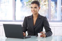 Attractive businesswoman smiling in bright office Stock Photo