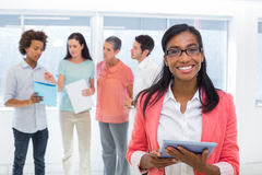 Attractive businesswoman smiling at camera while colleagues are standing behind Royalty Free Stock Image