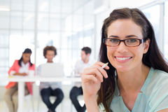Attractive businesswoman smiling at camera with coworkers in background Royalty Free Stock Photography