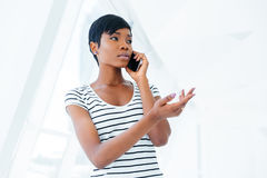 Attractive businesswoman standing in office and talking on cell phone Royalty Free Stock Images