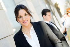 Attractive businesswoman standing outside of company building. C Stock Photos