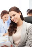 Attractive businesswoman taking notes in office Stock Photos