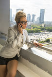 Attractive  businesswoman talking on her phone on the balcony of the new multi-storey house. Stock Photos
