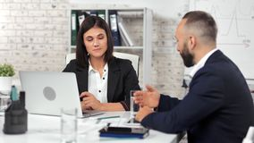 Attractive businesswoman talking with male employee having corporate team meeting at modern office. Medium shot. Female boss and male colleague collaboration stock footage