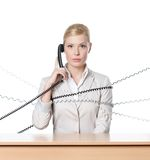 Attractive businesswoman tied with phone wire. Young businesswoman sitting at a office desk tied with phone cord, isolated Stock Photography