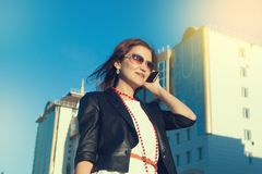 Attractive businesswoman using a cell phone in the city in sanny day. Young attractive businesswoman using a cell phone in the city in sanny day royalty free stock photo