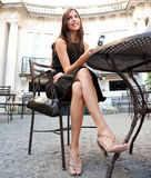Businesswoman with cell in cafe. Attractive businesswoman using a cell phone while sitting in a luxurious coffee shop terrace, outdoors Stock Photos