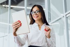 Attractive businesswoman using a digital tablet while standing in a large corporate building royalty free stock photos