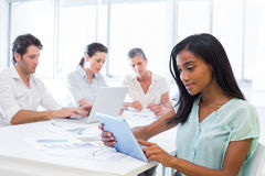Attractive businesswoman using tablet with coworkers behind Stock Photo