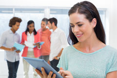 Attractive businesswoman using tablet with coworkers behind Stock Photos