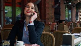 Attractive Businesswoman wearing Suit using Smartphone in an outdoor Cafe, drinking Coffee. SLOW MOTION. Professional stock footage