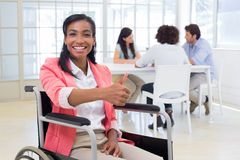 Attractive businesswoman in wheelchair gives thumbs up to camera Royalty Free Stock Images