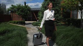 Adult woman carrying suitcase walking to car. Attractive businesswoman in white blouse and high heeled shoes carrying suitcase on wheels to car, standing near stock video