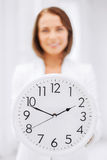Attractive businesswoman with white clock Stock Photography