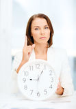 Attractive businesswoman with white clock Stock Images