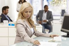 Attractive businesswoman working at desk Royalty Free Stock Photos