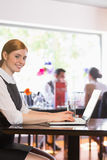 Attractive businesswoman working on laptop smiling at camera Royalty Free Stock Photo