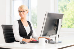 Attractive businesswoman working in the office by the computer Stock Photography