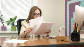 Attractive businesswoman works with documents with her own thoughts. 4K.