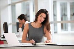 Attractive businesswoman writing in agenda Stock Photo