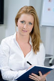 Attractive businesswoman writing in notebook Stock Photo