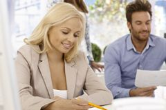 Attractive businesswoman writing notes Stock Photo