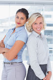 Attractive businesswomen with arms crossed standing back to back Royalty Free Stock Photos