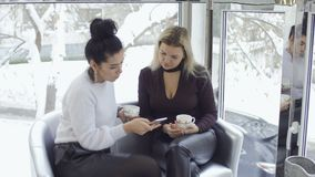 Attractive businesswomen dicussing something looking at phone. Two businesswomen drinks coffee and talking sitting on the sofa near the window. Pretty females stock video