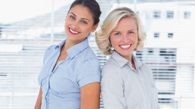 Attractive businesswomen standing back to back Stock Photos