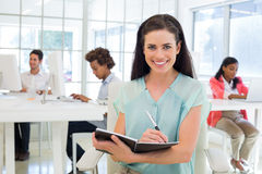 Attractive businesswomen writing in notebook with colleagues behind her Royalty Free Stock Image