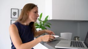 Attractive woman using her laptop while having a breakfast. Attractive busy woman using her laptop while having a breakfast stock video