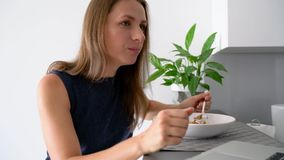 Attractive woman using her laptop while having a breakfast. Attractive busy woman using her laptop while having a breakfast stock video footage