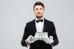 Attractive butler in tuxedo and gloves holding money on tray. Attractive young butler in tuxedo and gloves holding money on tray royalty free stock photos