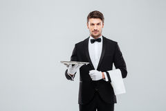 Attractive butler in tuxedo standing and holding silver empty tray stock photography