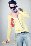 Attractive call center guy with colorful phones Royalty Free Stock Images
