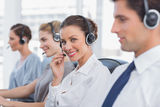 Attractive call centre agent with a headset. With colleagues working around Stock Photography