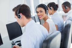 Attractive call centre employee looking over shoulder. While wearing a headset Stock Photography