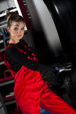 Attractive Car Mechanic. A beautiful woman wearing a car mechanic uniform, working in a garage with a tire Royalty Free Stock Photos