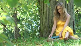 Attractive carefree girl sit under tree and read books in park on sunny summer day. 4K stock video