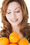 Attractive casaual woman holding oranges. Royalty Free Stock Photos