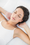 Attractive casual brunette in white pajamas resting on her bed Stock Photography