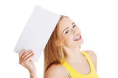 Attractive casual caucasian woman holds empty white piece of pap Royalty Free Stock Images