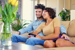 Attractive casual couple sits on a couch and switching tv channels with remote control. The attractive casual couple sits on a couch and switching tv channels royalty free stock photo