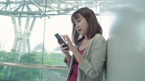 Attractive casual happy young Asian woman in international airport, using and checking her smartphone standing in terminal hall. Attractive casual happy young stock video