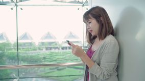 Attractive casual happy young Asian woman in international airport, using and checking her smartphone standing in terminal hall. Attractive casual happy young stock video footage