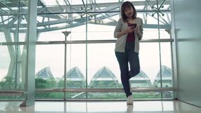Attractive casual happy young Asian woman in international airport, using and checking her smartphone standing in terminal hall. Attractive casual happy young stock footage