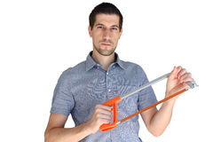 Attractive casual young man holding a hand saw. A portrait of attractive casual young man holding a hand saw Royalty Free Stock Photos