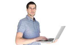 Attractive casual young man holding laptop. A portrait of attractive casual young man holding laptop Royalty Free Stock Photos