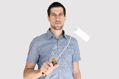 Attractive casual young man holding a paint brush. A portrait of attractive casual young man holding a paint brush Royalty Free Stock Photo